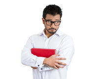 Young worried nervous guy with big glasses carrying book Stock Photos