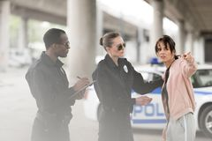 Young worried woman pointing by finger to policewoman and policeman writing. In clipboard royalty free stock photos