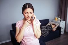 Young worried woman stand in room nd talk on phone. Sick child lying on couch behind. She sleeps. Young worried women stand in room nd talk on phone. Sick child stock photo