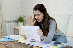 Young worried woman suffering stress doing domestic accounting paperwork bills royalty free stock photography