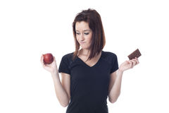 Young worried woman torn between a chocolate bar and fresh apple Royalty Free Stock Photography