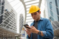 Young foreman engineer worker using smartphone. Young worry foreman engineer worker with yellow helmet using smartphone or mobile phone to check construction stock photos