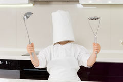 Young would be chef clowning around. Holding a ladle and potato masher in his hands wearing an adult chefs hat that is completely covering his face stock images