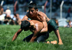 A young wrestler attempts to overpower his opponent at the Elmali turkish Oil Wrestling Festival in Turkey. Royalty Free Stock Image