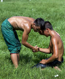 A young wrestler consoles his opponent after victory at the Kirkpinar Turkish Oil Wrestling Festival in Edirne, Turkey. Royalty Free Stock Photos