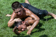A young wrestler is forced to the ground by his opponent at the Elmali Turkish Oil Wrestling Festival, Turkey. Stock Image
