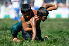Young wrestlers battle for victory at the Elmali Turkish Oil Wrestling Festival in Turkey. Stock Photo