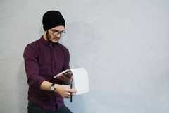 Young writer guy holding a pencil and notebook in hands. Dressed with black hat and wearing glasses. royalty free stock photos
