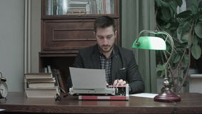 Young writer inserting paper into red vintage typewriter and starting typing stock video