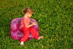 Young writing girl sits in inflatable armchair Royalty Free Stock Images