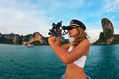 Young yacht captain measure boat position by navigational sextant. Young captain woman in cap on deck of sailing yacht taking sight in sextant to measure boat Royalty Free Stock Images