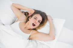 Young yawning woman lying on her bed in bedroom Royalty Free Stock Images