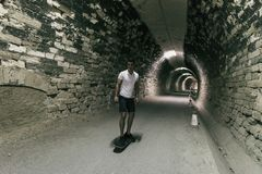 Young 20-25 years old man in tunnel with skateboard. Ambient light image (IMAGE HAVE SOME NOISE). Young 20-25 years old man in tunnel with skateboard. Ambient stock image