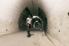 Young 20-25 years old man in tunnel with skateboard. Ambient lig royalty free stock images