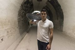 Young 20-25 years old man in tunnel with skateboard. Ambient lig royalty free stock photo