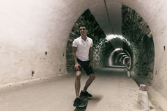 Young 20-25 years old man in tunnel with skateboard. Ambient lig stock photos