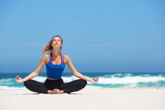 Young yoga woman sitting in lotus pose at the beach Stock Photos