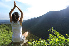 Young yoga woman at sunrise mountain Stock Images