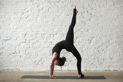 Young yogi attractive woman in Bridge pose, white loft backgroun Stock Photo