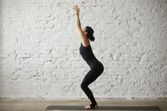 Young yogi attractive woman in Chair pose, white loft background. Young yogi attractive woman practicing yoga concept, standing in Utkatasana exercise, Chair Stock Photo
