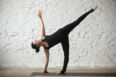 Young yogi attractive woman in Half Moon pose, loft background Stock Image