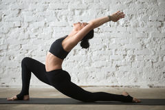 Young yogi attractive woman in Horse rider pose, loft background. Middle aged yogi attractive woman practicing yoga concept, standing in Horse rider exercise stock images