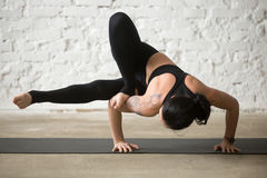 Young yogi attractive woman in Maksikanagasana pose, white loft Stock Photos