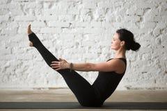 Young yogi attractive woman in Paripurna Navasana pose, white ba Stock Image