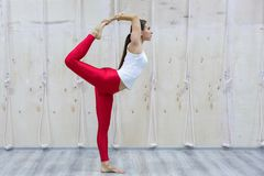 Young yogi attractive woman practicing yoga concept, standing in Natarajasana exercise stock photos