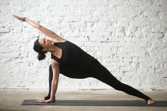 Young yogi attractive woman in Utthita parsvakonasana pose, loft. Young yogi attractive woman practicing yoga concept, standing in Utthita parsvakonasana Royalty Free Stock Image