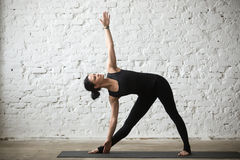 Young yogi attractive woman in Utthita Trikonasana pose, white l. Young yogi attractive woman practicing yoga concept, standing in Utthita Trikonasana exercise Stock Photo