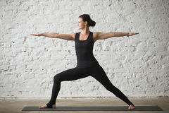 Young yogi attractive woman in Warrior Two pose, loft background Stock Photos
