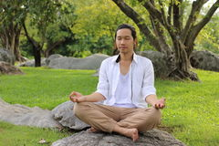 Young yogi man doing yoga meditation while sitting in lotus position on the rock in the park. Royalty Free Stock Image