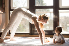 Young yogi mother and baby daughter sitting near, healthy day. Young attractive smiling yogi mother working out, exercising, baby daughter sitting near Royalty Free Stock Photos