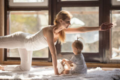 Young yogi mother in Bird dog pose, baby daughter near Royalty Free Stock Images