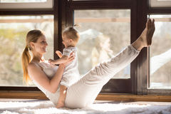 Young yogi mother in boat pose with her baby daughter Stock Photo