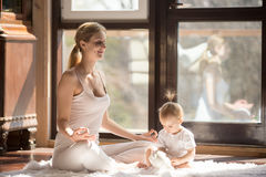 Young yogi mother in Easy Seat pose, baby daughter near Stock Photos