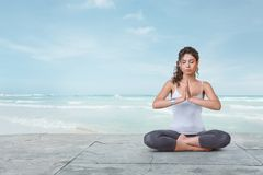 Young woman is meditating on the beach Stock Image