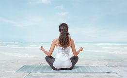 Young woman is meditating on the beach Royalty Free Stock Photography