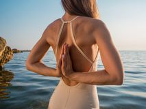 Young yogi woman practicing yoga, standing in sea with Namaste behind the back, working out wearing white swimsuit royalty free stock photo