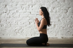 Young yogi woman in seiza pose with namaste, loft background Royalty Free Stock Images