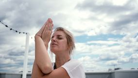 Young yogini woman meditate with hands in Namaste mudra in slow motion. In background of white clouds and bright blue sky. Camera is shooting face from below stock video