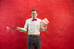 Young young funny man with flowers and gift Stock Images