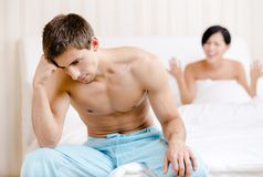 Young young married couple argues in bed. Young couple argues in bed. Depressed young men sitting on the edge of the bed. Focus on man Royalty Free Stock Photo
