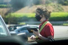 Free Young Youthful Fast Food Worker Working At Chick-fil-a Drive Through Amidst Cars Take Orders With Tablet Stock Images - 179335764