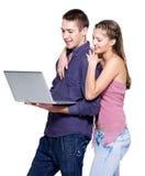 Youngcouple die laptop bekijkt stock foto's