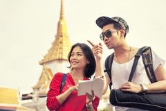 Younger asian tourist holding guide book standing in traveling d Stock Photos