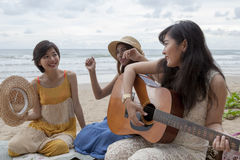 Younger asian woman friend vacation relaxing playing guitar and Royalty Free Stock Images