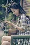 Younger asian woman and smart phone in hand chat social media ha Stock Image