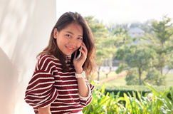 Younger asian woman talking on smart phone with happiness emtion royalty free stock photos